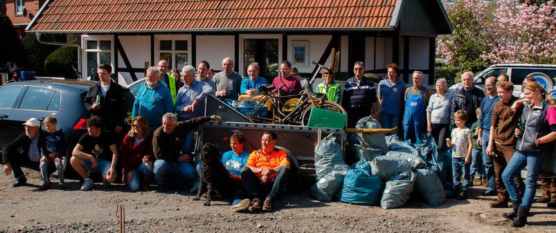 Um einen Autoanhänger mit Müll, wie rostiges Rad, Plastikkisten und Müllsäcken, haben sich viele Müllsammlerinnen und -sammler für ein Abschlussfoto der Aktion gestellt.