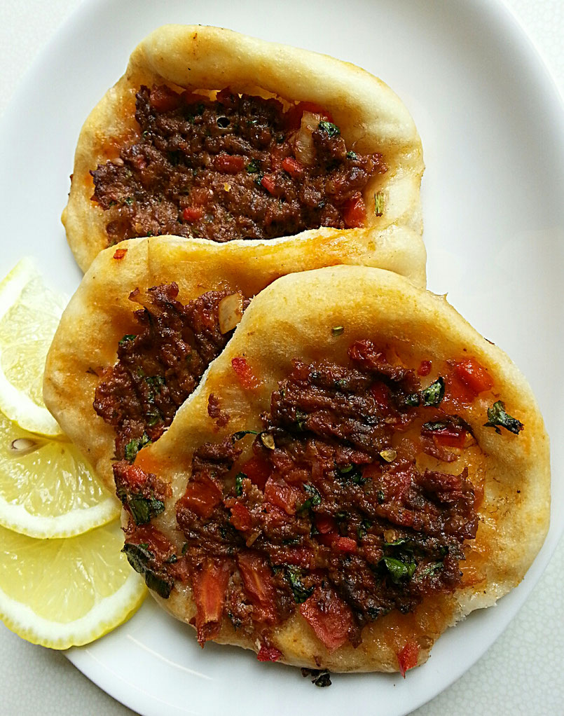 Mini Lahmacun mit frischen Kräutern und aromatischen Tomaten