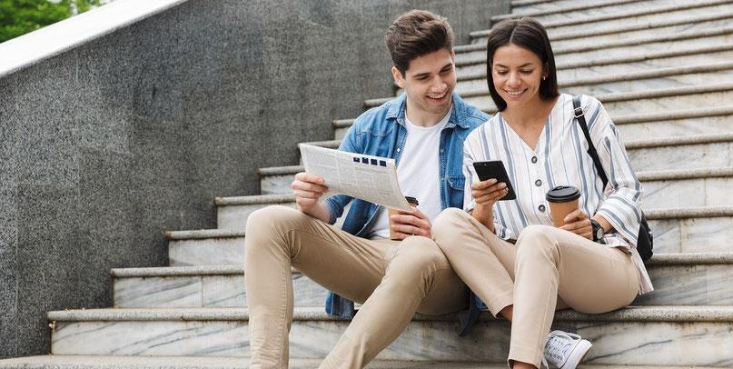 Ein Mann und eine Frau mit Zeitung und Handy sitzen auf den Stufen im Ausland. Gut abgesichert mit einer günstigen Reiseversicherung für Langzeit-Aufenthalte ohne Selbstbeteiligung der ERGO.