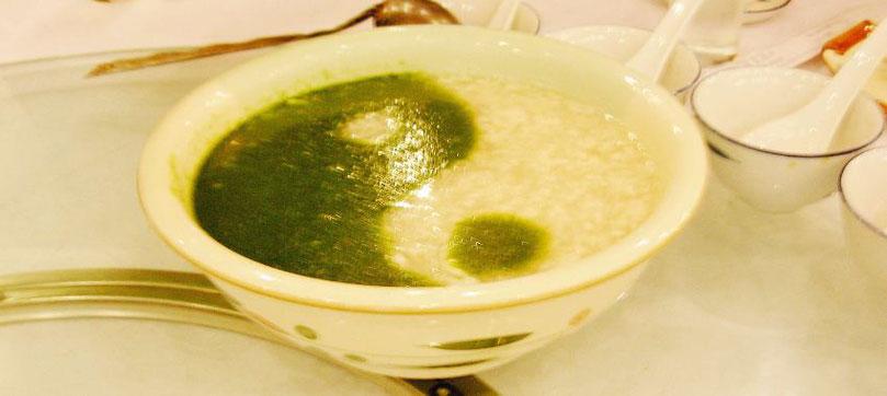 Ein Teller Suppe grün und hell angerichtet als Yin-Yang-Zeichen