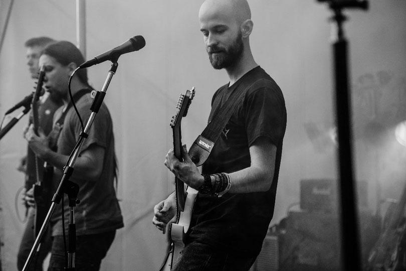 Musiker einer Metalband auf einer Bühne mit Gitarre und Mikrofonen
