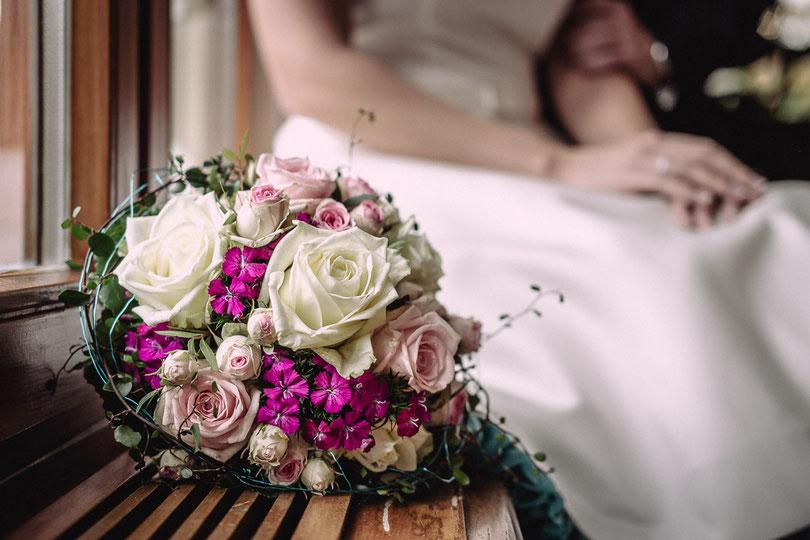 Ein farbenfroher Brautstrauß vor einem sich umarmenden Hochzeitspaar
