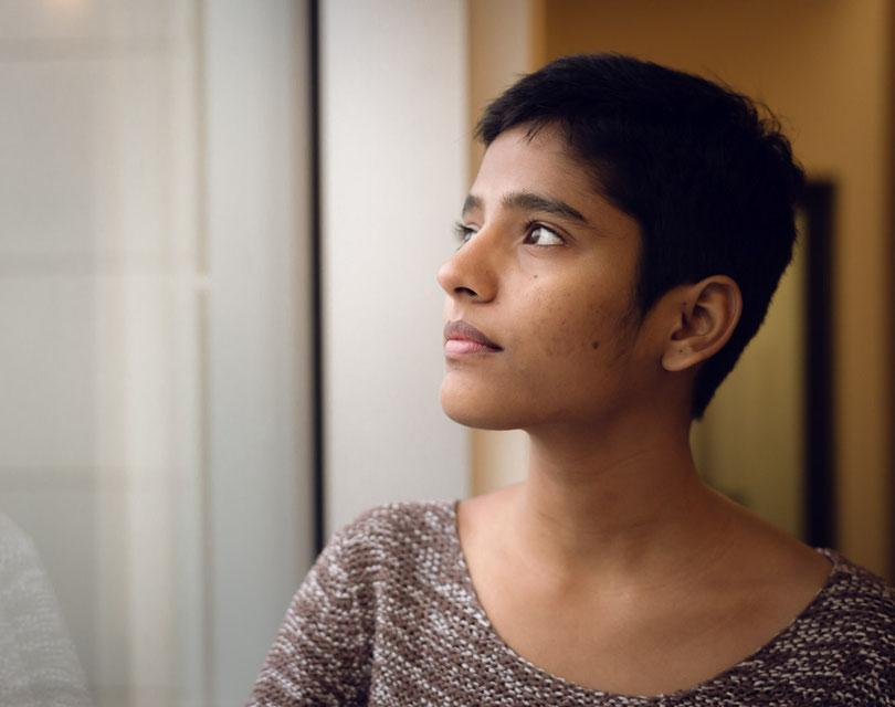 Schönes Bild einer jungen dunkelhaaringen Frau die aus einem Fenster blickt