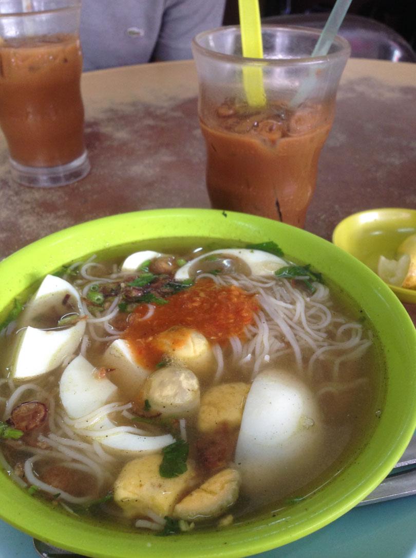 Malaiische scharfe Nudelsuppe mit Ei und etwas Gemüse. Unser Lieblingsgericht, mit viel zu süssen Kaffee