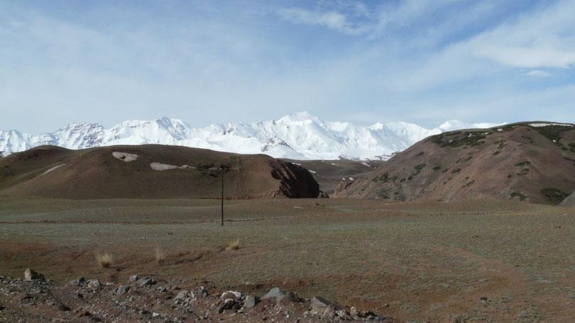 Les collines kirghizes devant la chaine des Pamirs