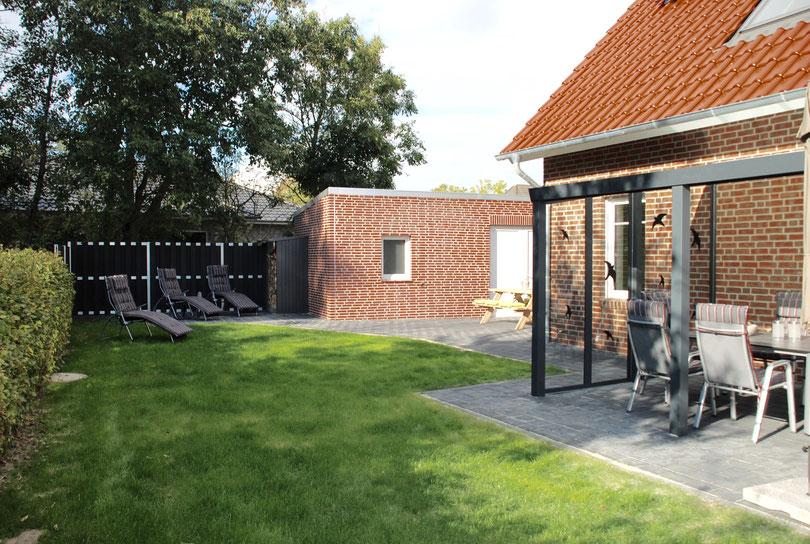 Terrasse mit Liegestühlen und Holzlager und Grill