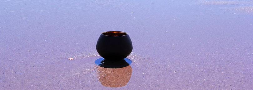 Teetasse am Strand im Wasser