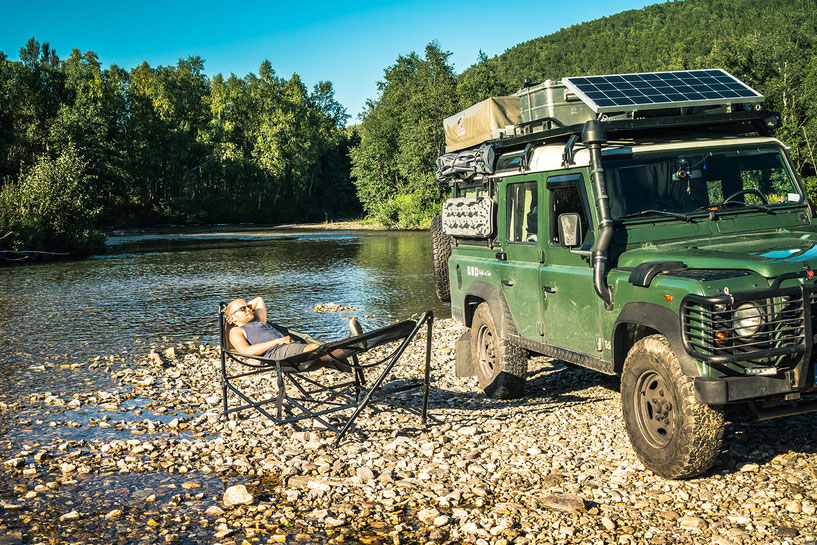 Relaxing in the Tembo hammock near a river with the Land Rover Defender