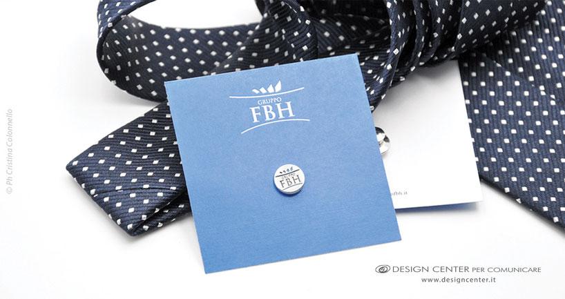 Spilla Gruppo FBH in oro bianco e smalti in cartonino-dedica personalizzato. Sullo sfondo cravatta moda
