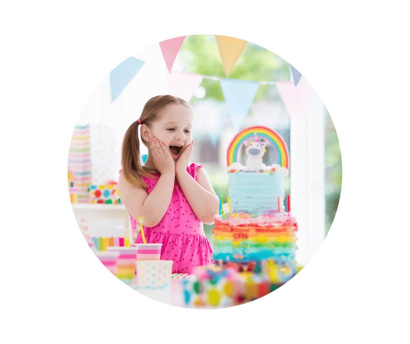 Ein kleines Mädchen freut sich über eine traumhaft schöne Regenbogen-Geburtstagstorte.