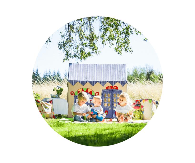 Kinderbetreuung bei Entertainment for Kids. Drei Kinder sitzen auf einer Wiese vor einem wunderschönen Spielhaus.
