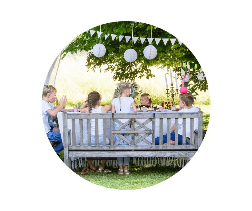 Kinderbetreuung bei Entertainment for Kids. Mehrere Kinder sitzen an einem schön dekorierten Tisch und essen Kuchen.