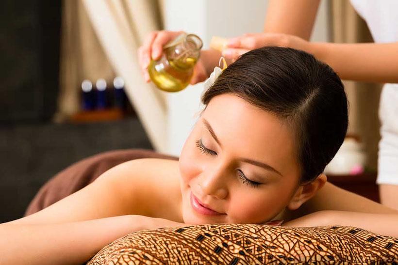 Thai Aroma Öl Massage. Öl wird auf den Körper einer Frau geträufelt.