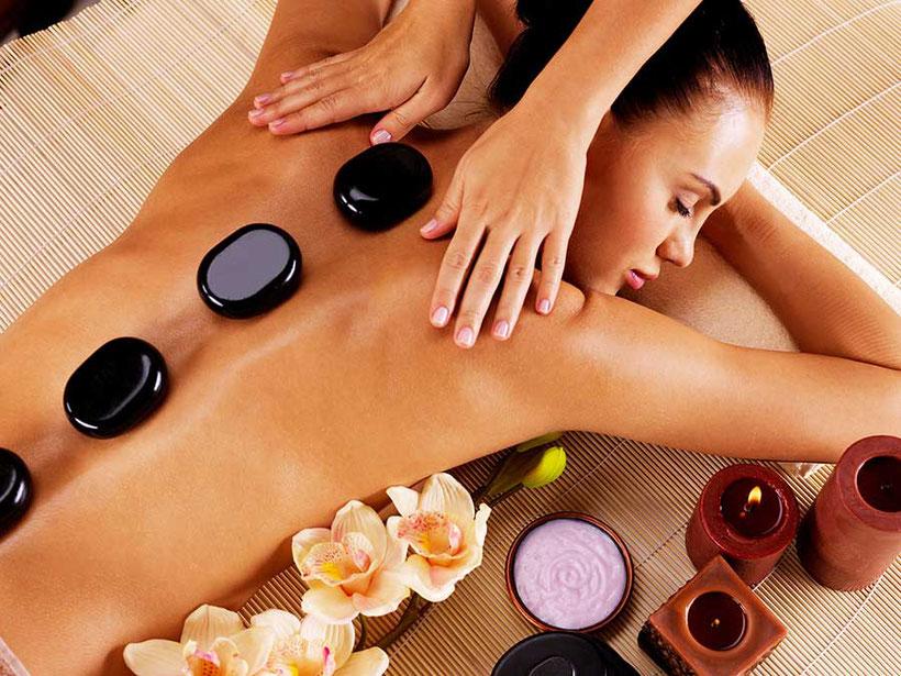Hot Stone Massage. warme Steine liegen auf dem Rücken einer Frau