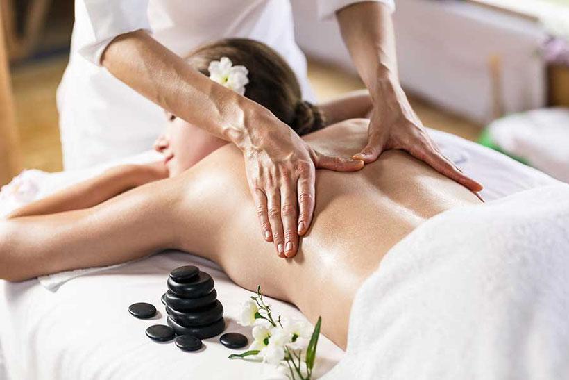 Rücken Massage. Frau liegt auf dem Bauch und wird massiert