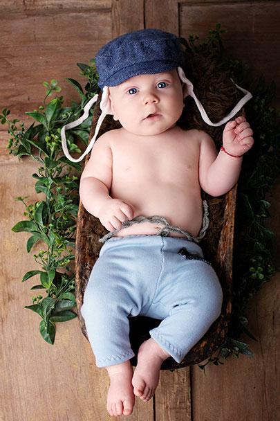 Baby liegt in einem Stuhl, hat eine Mütze auf