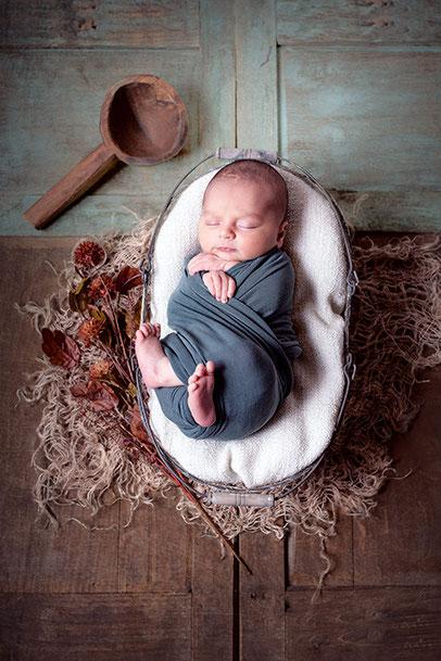 Babyfoto in einer Holzschale, mit einem Tuch gewickelt