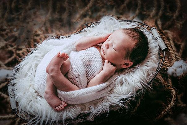 Baby liegt eingewickelt, schlafend auf einem Holzbett