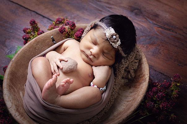 Baby liegt in einem Eimer und hat eine Mütze auf