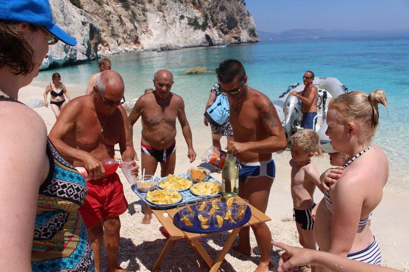 Sergio kommt mit dem Beiboot. Kleine Vorspeisen und Aperitif am Strand