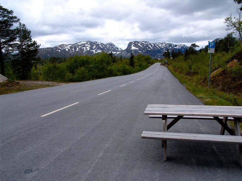 Schneebedeckte Berge im Juni und eine Raststätte