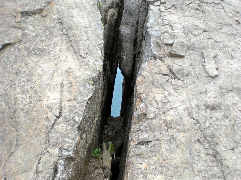 Felsspalte am Boden. Unter uns blitzt der blaue Fjord