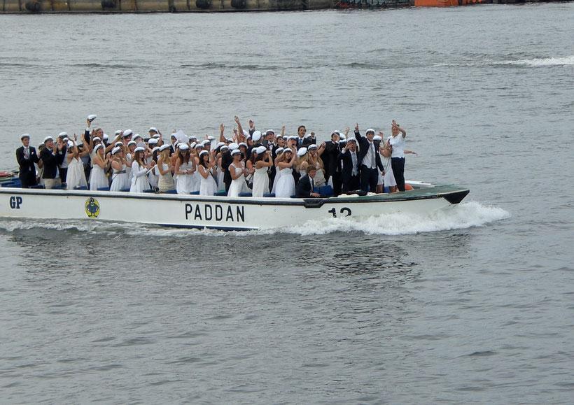 Teilnehmer der Abschlussfeier, erst mit Boot und dann im offenen LKW durch die Stadt