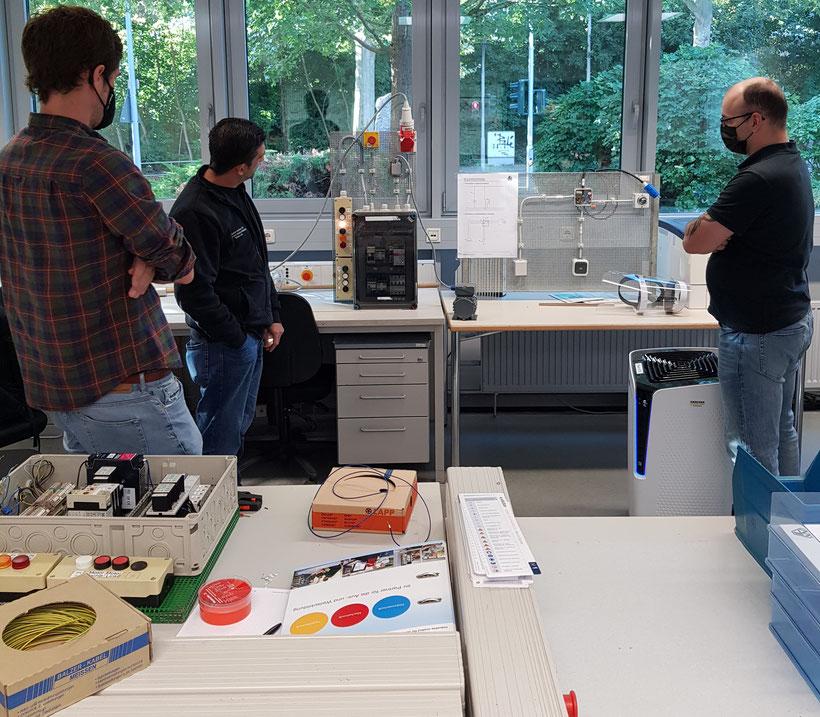 Ein Ausbilder des ILW Mainz erläutert EUP-Kursteilnehmern eine Schaltung zur Steuerung eines Elektromotors, die sie anschließend nachbauen werden.