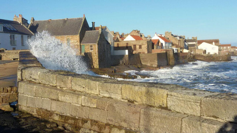 Waves splashing over the wall at Anstruther harbour