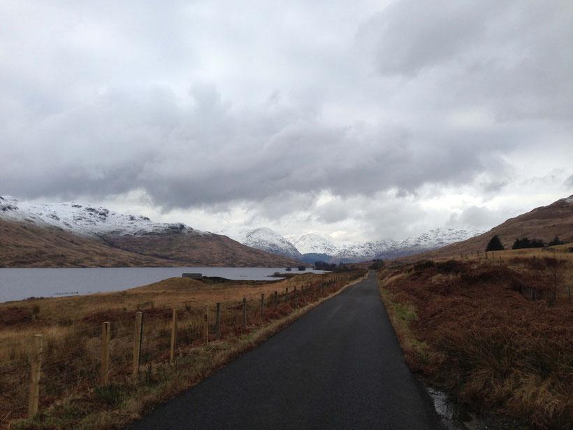 Düstere Wolken und schneebedeckte Gipfel an Loch Arklet im Februar