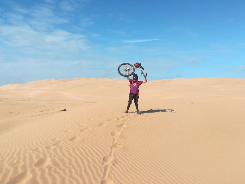 Spanier der mit dem Einrad in der West-Sahara unterwegs ist