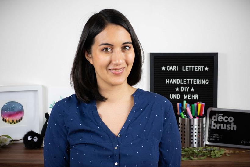 Bild von Cari an ihrem Arbeitsplatz umgeben von Stiften