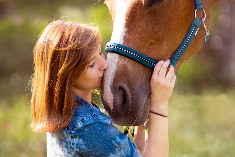 Mädchen kuschelt mit Pferd