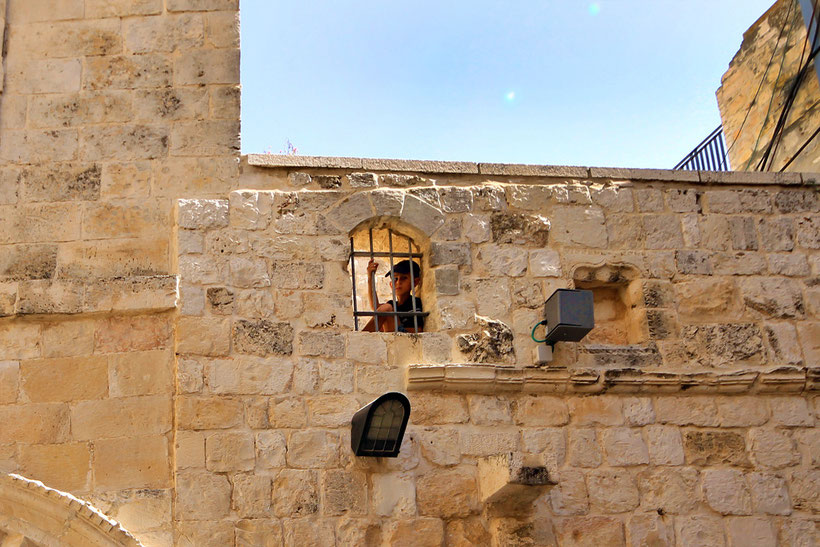 A boy looking from his window in The Old City in Jerusalem, Israel © Sabrina Iovino | JustOneWayTicket.com