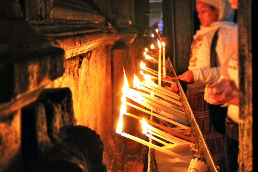 Lightning candles inside the Church of the Holy Sepulchre in Jerusalem, Israel © Sabrina Iovino | JustOneWayTicket.com