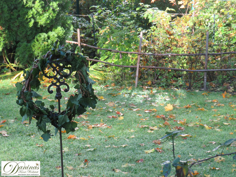 Herbstkranz aus Weinreben mit Efeu am frostigen Morgen im Garten