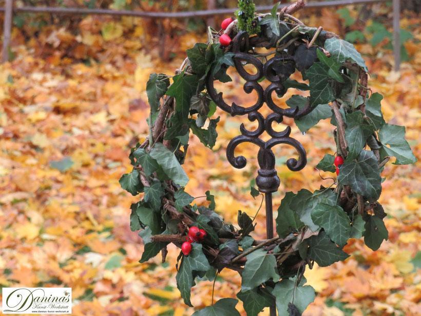 Herbstkranz aus Weinranken mit Efeu und Hagebutten vor gefallenem gelben Laub