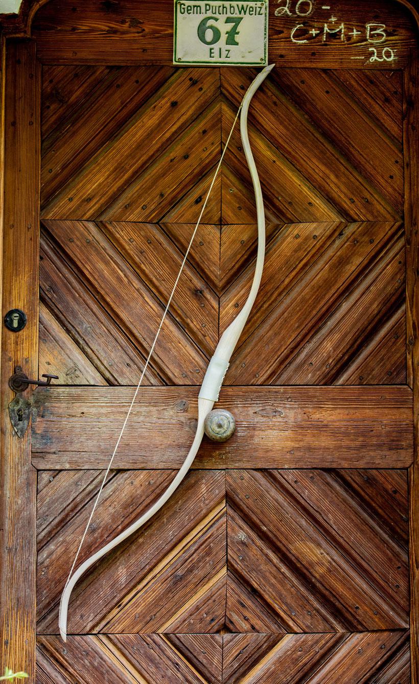 Weißer Reiterbogen mit Pfeileset am Holzstoß