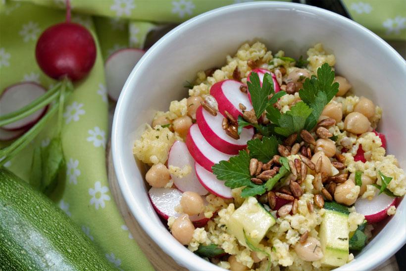 Rezeptfoto Low Carb Radieschen-Salat: Schüssel mit Hirse, Kichererbsen, Radieschen in Scheiben, Zucchini Würfel mit Petersilie. Neben der Schüssel liegt eine Zucchini und ein Radieschen mit grün.