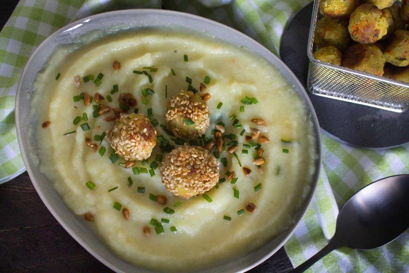Von oben betrachtet: ein grauer Teller mit einer gelben Suppe, grünen Kräutern und Klößchen mit Sesam auf einer grün weiß karierten Tischdecke und ein dunkler Löffel