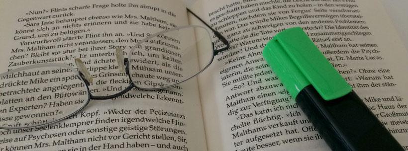 aufgeklapptes Buch mit einer Brille und Stift