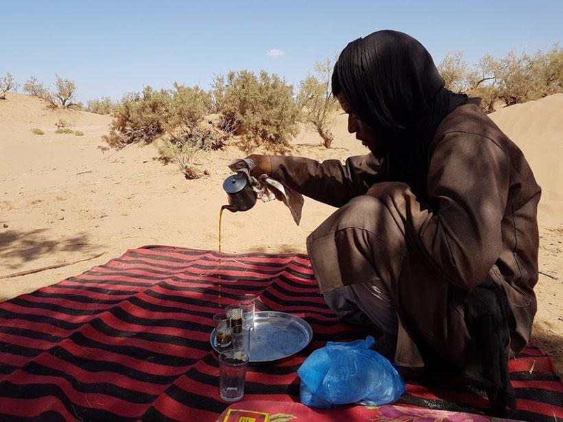 Nomade qui prépare le thé dans le désert