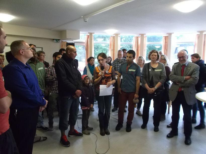 """Im großen Aufenthaltsraum haben sich Gastgeber und Gäste versammelt. Cornelia Meyer vom Flüchtlingsnetzwerk """"Willkommen in Neu Wulmstorf"""" (Mitte) bedankt sich bei allen für den gelungenen Auftakt des Festes. (Foto: Courage e.V.)"""
