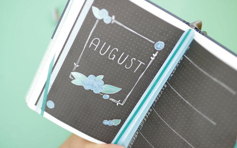 [Werbung] Mein Monthly Spread / Monthly Grid / Monatsübersicht im Bullet Journal auf Black Pages. Für schwarzes Papier eignen sich die edding Gelroller besonders gut. Weißer Gelroller für das Handlettering und bunte Gelroller für die Blaubeer Illustration