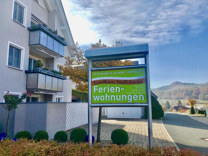"""Hausfront vom Landhaus Staffelstein mit seinen Ferienwohnungen und Parkplatz mit """"Weinhügel"""" im Hintergrund"""