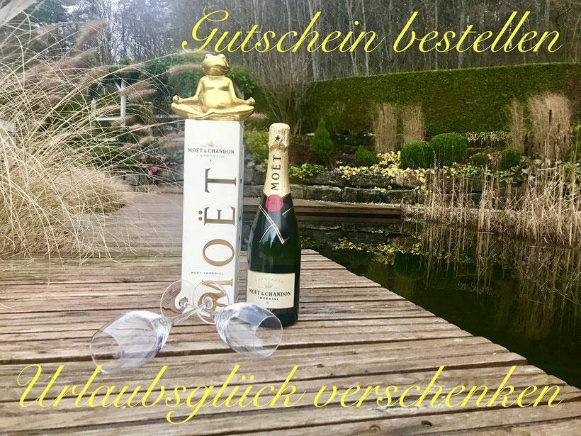 eine Flasche Sekt mit Sektgläsern am Badeteich und entspannten goldenen Frosch in Meditation Pose