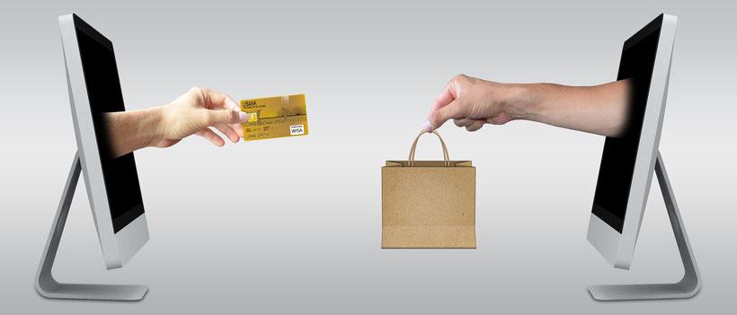 Zwei Bildschirme aus denen Hände kommen. In der einen Hand ist eine Kreditkarte und in der anderen eine Einkaufstüte.