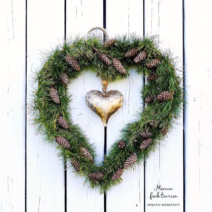 Aufgehängter Kranz in Herzform mit Lärchenästen und Zapfen in der Mitte ein goldenes Herz