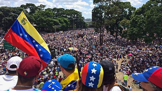 Manifestanti pro-Maduro con un cartello raffigurante Chavez