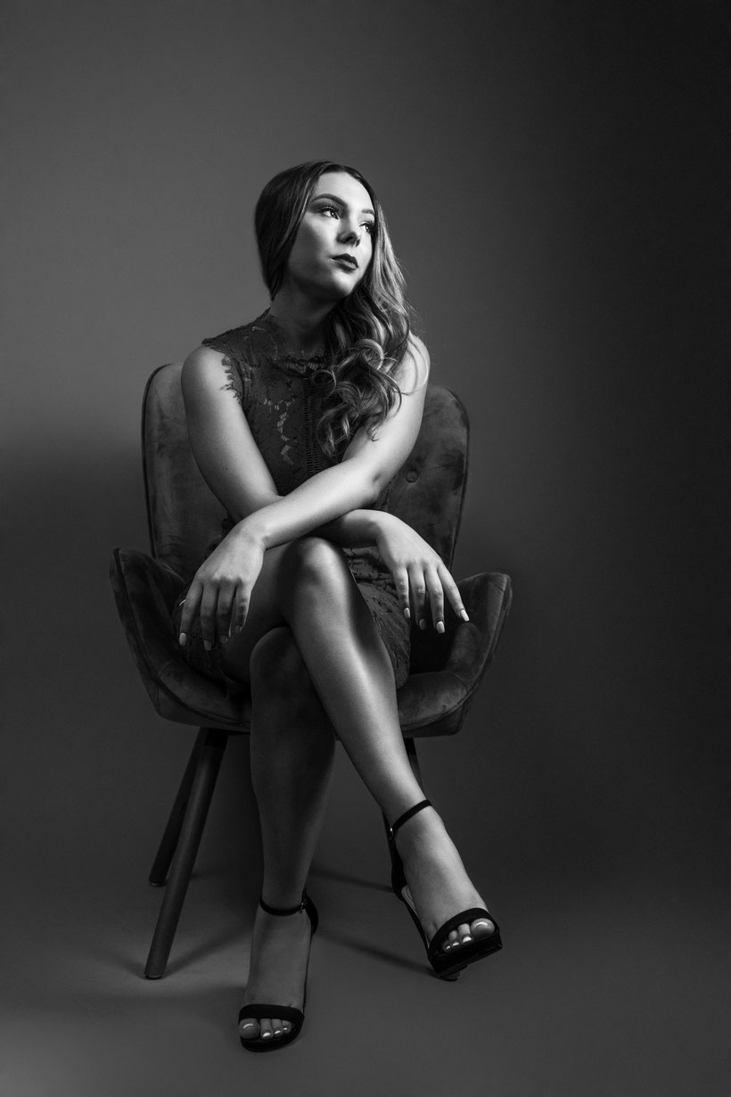 black and white image young teen girl sitting with legs crossed and arms crossed over knee looking up to the right at the light, deep in thought